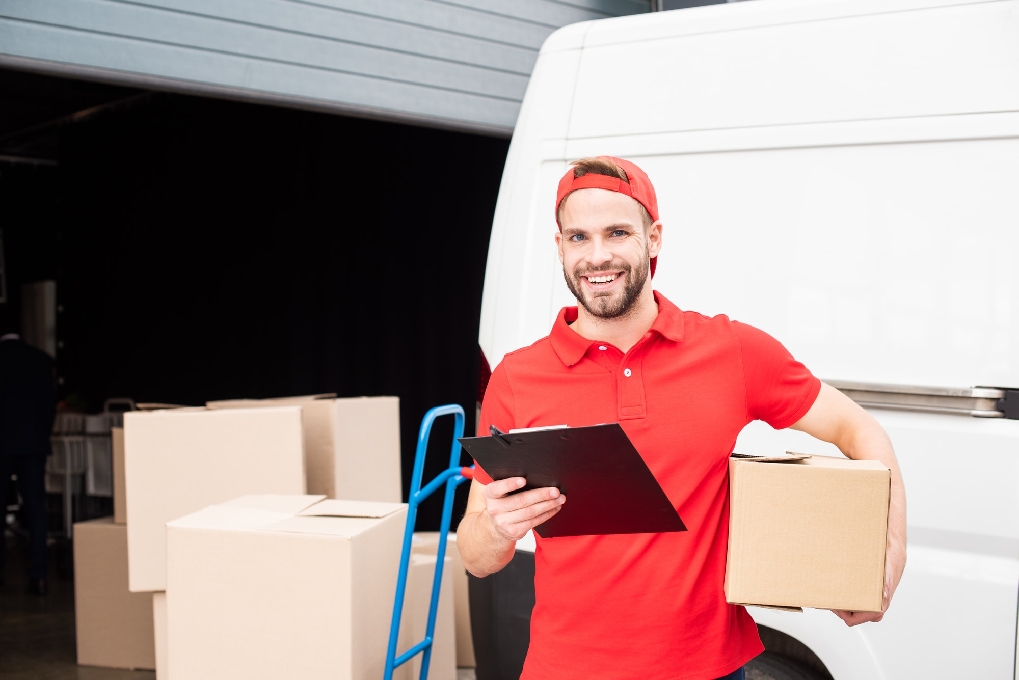 portrait of young smiling delivery man with cardboard box and notepad